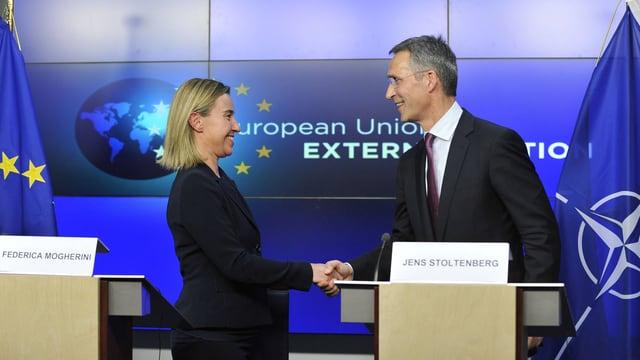 Mogherini und Stoltenberg geben sich anlässlich einer Medienkonferenz hinter ihrn Rednerpulten die Hand, im Hintergrund Nato- und EU-Flagge.