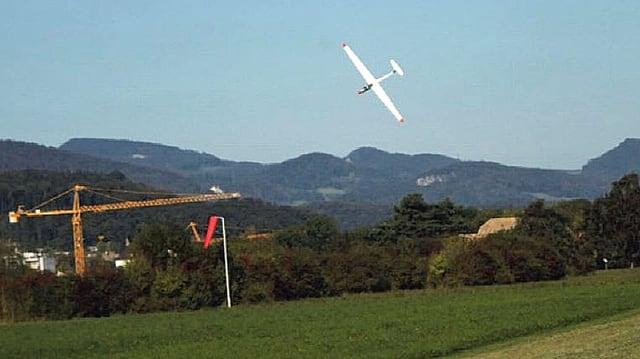 Weisses Segelflugzeug mit Nase nach unten kurz über einer Wiese.