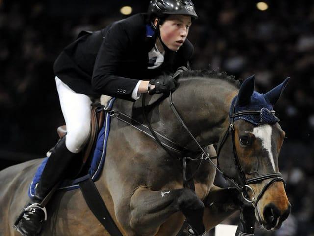 Ein junger Mann springt mit einem Pferd über ein Hindernis.