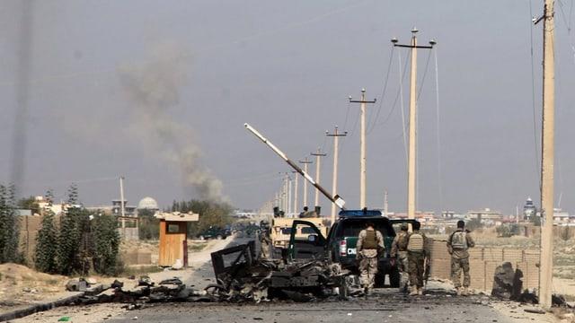 Afghanische Soldaten laufen an einem ausgebrannten Fahrzeug vorbei