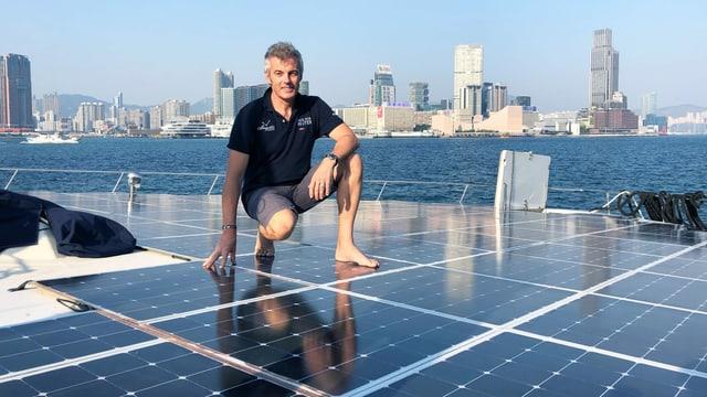 Ein Mann steht auf Solarpanels auf einem Katamaran.