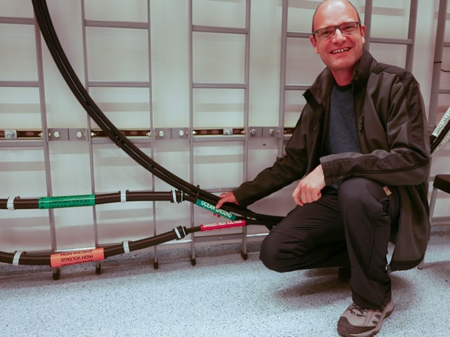 Das Bild zeigt Redaktor Reto Widmer, wie er das Farice-Kabel mit der Hand umfasst. Das Kabel verbindet Dänemark mit Island - es ist das wichtigste Kommunikationskabel für Island.