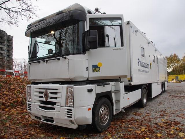 Ein grosser Lastwagen mit Anhänger steht auf einem Kiesfeld.