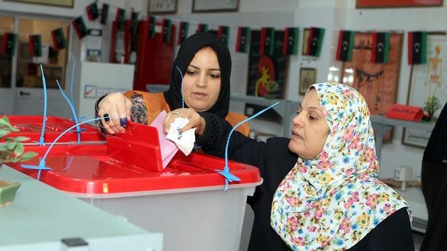 Zwei Frauen an einer Wahlurne