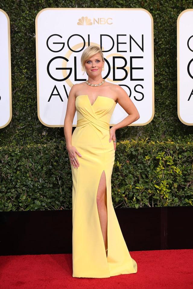 Reese Witherspoon posiert in einem gelben langen Kleid auf dem roten Teppich.