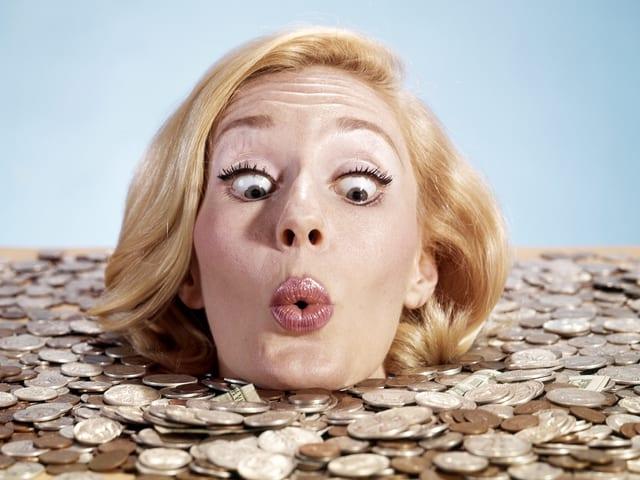Eine Frau steckt bis zum Hals im Geld und schaut es mit grossen Augen an.