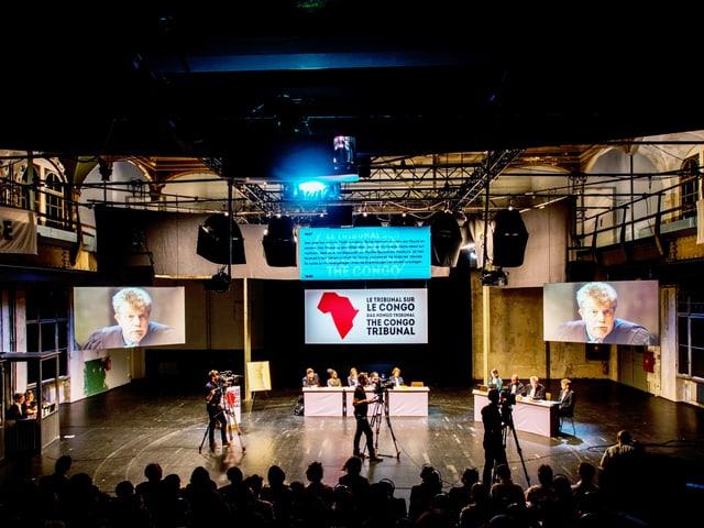 Grosser Theaterraum mit Leinwänden, Kameras und zwei Tischen. Vorne: Publikum im dunkeln.