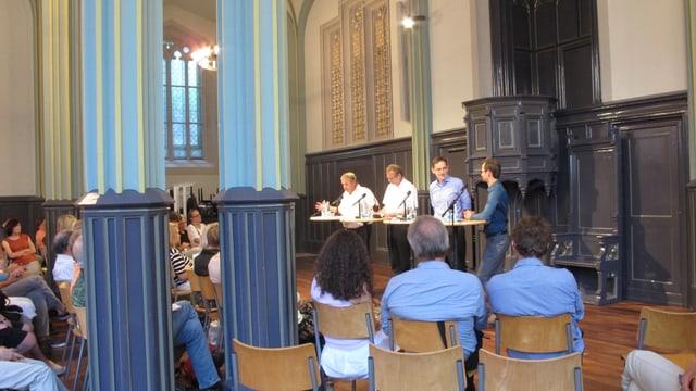 Vier Männer vor Publikum in einem Kirchenraum