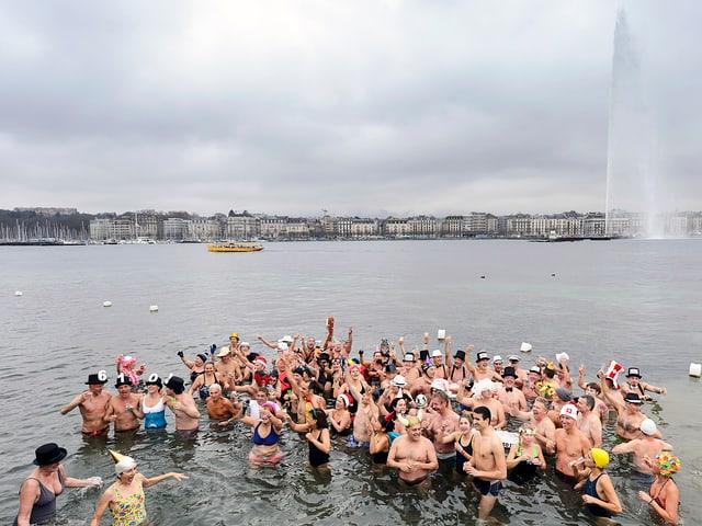 Eine Menschenmenge im Wasser prostet sich zu.