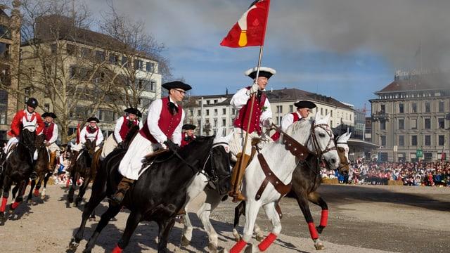 Zahlreiche Reiter umrunden dem Böögg mit der Standarte der Zunft Riesbach