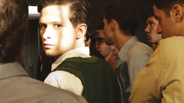 Ein Schauspieler schaut nach hinten über die Schulter mit ernstem Gesicht.