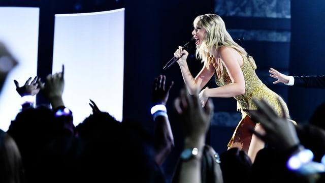 Eine blonde Frau steht auf der Bühne und singt