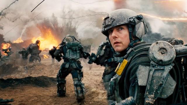 Tom Cruise in einem Kampfanzug. Hinten eine Explosion.