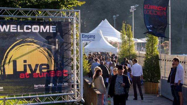 Blick auf den Festivaleingang mit vielen Leuten und einem grossen Festivalplakat.