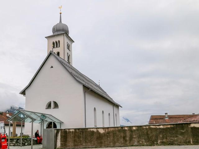 La baselgia refurmada da Castrisch cun ses tipic tetg da vaider a l'entrada.