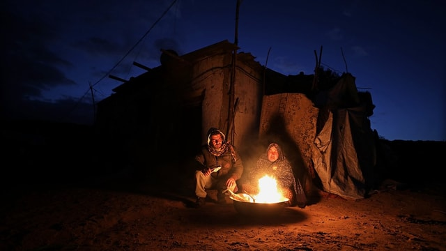 Zwei Menschen sitzen vor einem Zelt an einem Feuer.