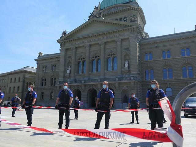 Absperrband und Polizisten mit Mundschutz vorm dem Bundeshaus.