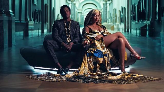 Jay-Z und Beyonce sitzen auf einem Sofa im Louvre.