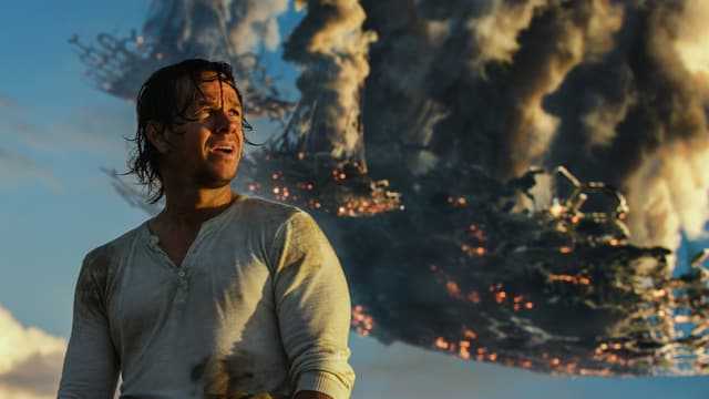 Der Filmheld vor einem abstürzenden Raumschiff.