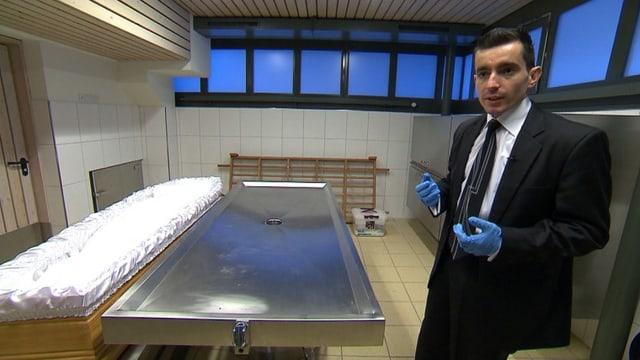 Enver Fazliji trägt einen Anzug und blaue Handschuhe, er steht in einem Leichenaufbahrungsraum.