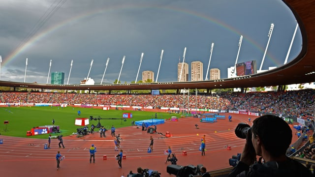 Blick in den Letzigrund mit Regenbogen im Hintergrund.