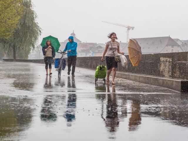 Drei Personen spazieren in starkem Regen