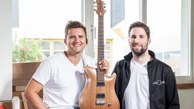 Zwei Junge Männer halten eine hölzerne E-Gitarre in den Händen.