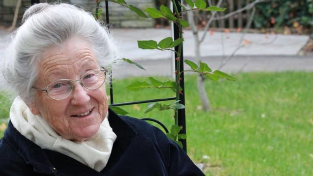 Margrit Reithaar auf Parkbank sitzend draussen im Grünen.