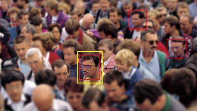 In einer Menschenmenge werden drei Gesichter durch rote und gelbe Computer-Kästchen hervorgehoben.