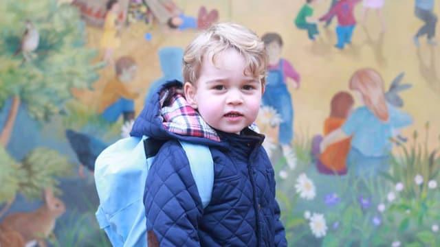 kleiner Junge posiert mit Rucksack vor einer farbigen Wand