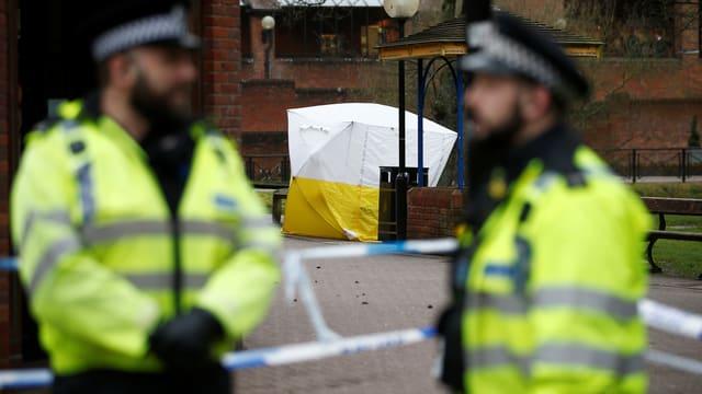 Zwei Polizisten in gelben Westen stehen vor einem Forensik-Zelt.