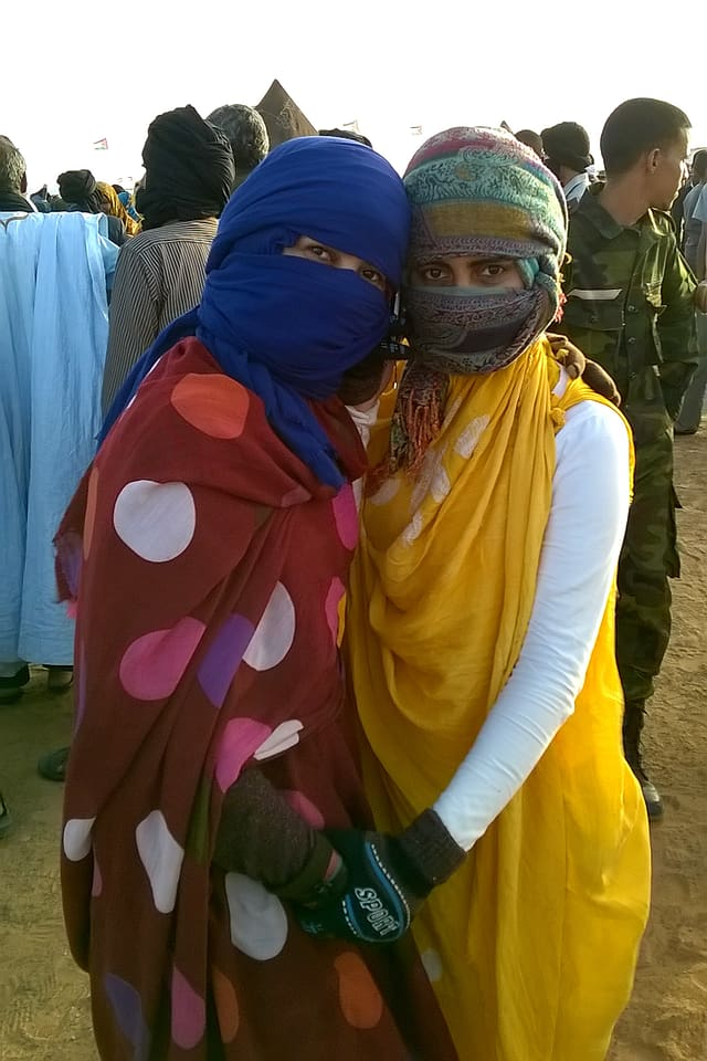 Zwei Frauen mit um den Kopf gebundenen Tüchern, für die Kamera posierend.