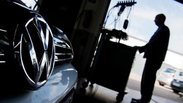 Auto da VW en garascha stgira cun lavurer.