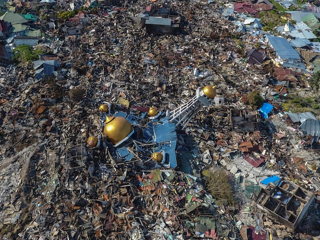 Zerstörte Häuser und in der Mitte eine kaputte Moschee mit einem goldenen Dach.