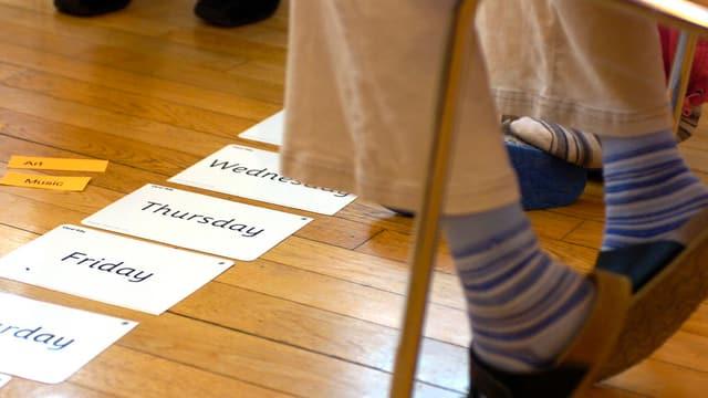 Ein Schüler mit Englisch-Kärtchen vor sich auf dem Boden.