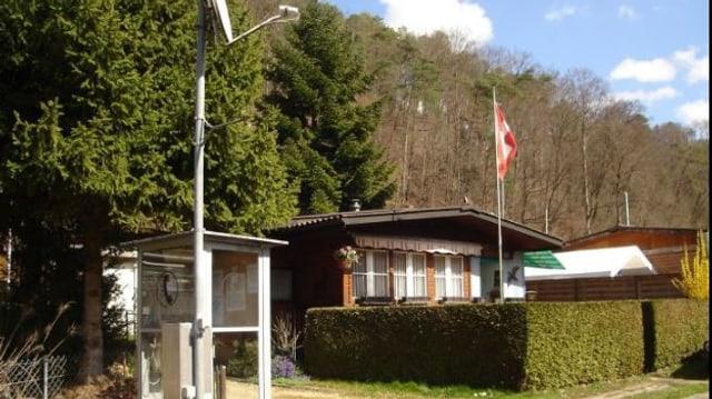 Blick auf ein Häuschen mit Schweizer Fahne am Fahnenmasten