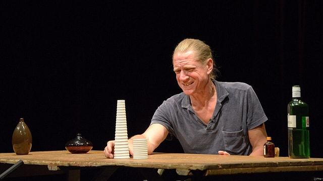 Ein Mann sitzt an einem Tisch mit verzerrtem Gesicht. Auf dem Tisch steht eine Flasche und viele kleine Sachen.