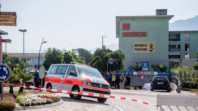 Ein Polizeiwagen vor einem Einfaukszentrum. Gegend ist mit Band abgesperrt.