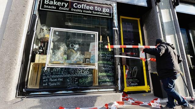 Notdürftig geklebtes Schaufenster eines Coffee-Shops, rot-weisse Absperrbänder.