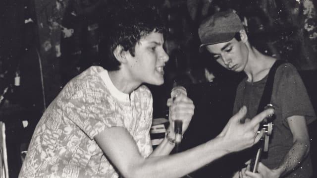 Schwarzweissfoto: Zwei junge Männer, einer mit Bass, der andere mit Mikrofon