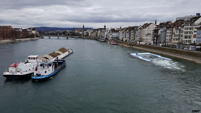 Blick auf den Rhein mit einem Schiff und der Surfwelle