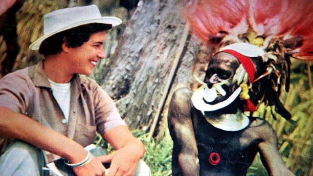 Eine Frau in Hemd und weissem Hut, mit einem Mitglied eines ursprünglichen Stammes sprechend.