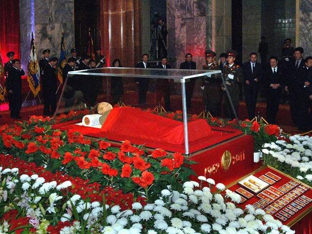 Kim Jong Il in einem Glassarg, darum herum rote und weisse Blumen.