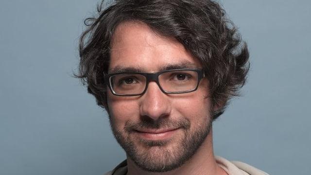 Pascal Pfister mit Dreitagebart, schwarzer Brille und dunklem, gewelltem Haar.