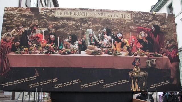Mitglieder der Basler Bebbi sitzen oder stehen an einem gedeckten Tisch, alle tragen Larven und ein kostüm.