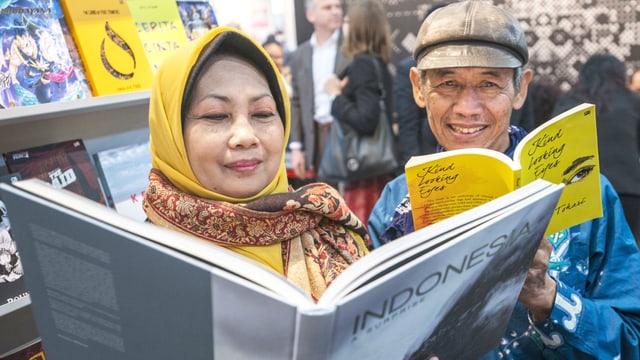 Neben einem Gestell mit Büchern lesen eine Asiatin und ein Asiate je in einem Buch.