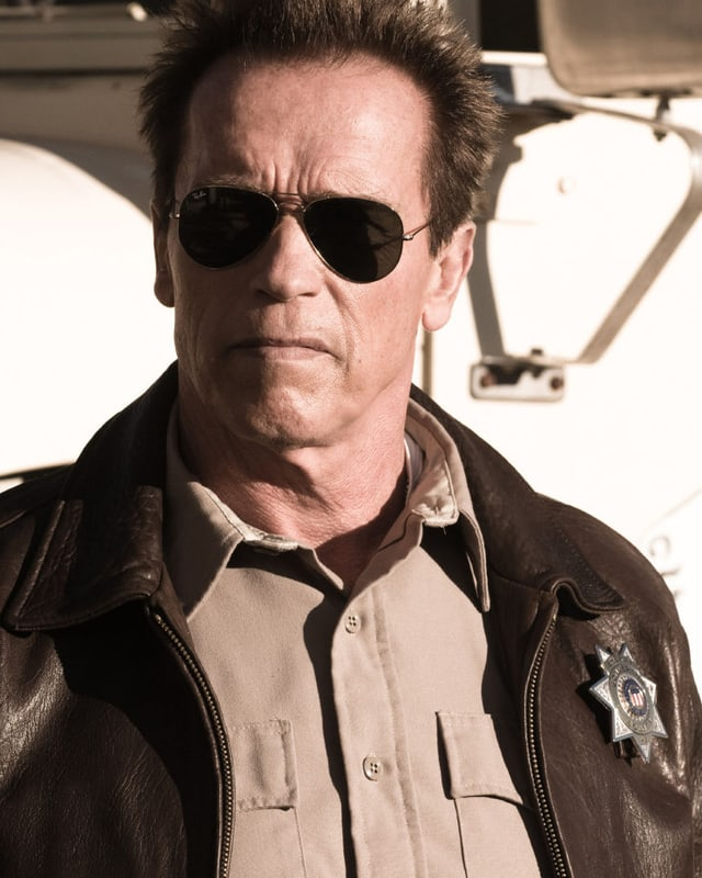 Arnold Schwarenegger mit Sonnenbrille guckt grimmig.