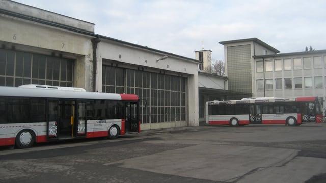 Graues Gebäude, davor ein rot-weisser Bus.