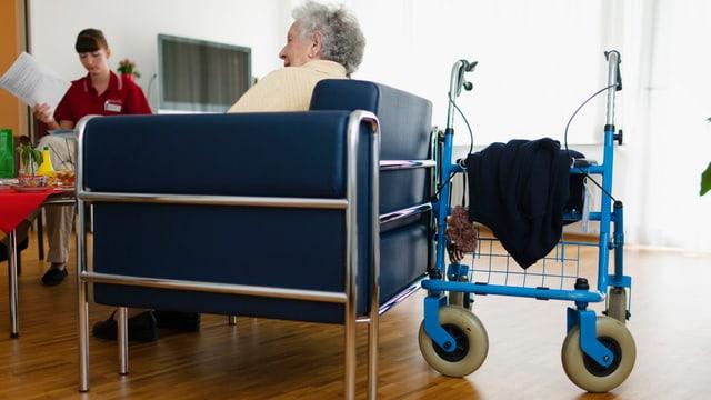 Eine ältere Frau auf einem Sessel.