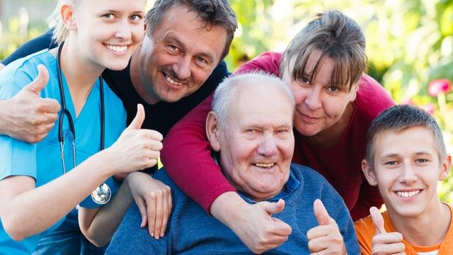 Familie mit pflegebedürftigem Senior auf Rollstuhl.